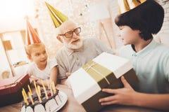 Nonno, nipote e nipote a casa I bambini stanno dando il regalo di compleanno immagine stock libera da diritti