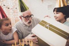 Nonno, nipote e nipote a casa I bambini stanno dando il regalo di compleanno fotografia stock libera da diritti