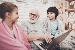 Nonno, nipote e nipote a casa Il nonno ed i bambini stanno guardando il film sul computer portatile fotografie stock libere da diritti