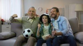Nonno, papà emozionante e figlio felici per il gioco di conquista della squadra di football americano nazionale, casa stock footage