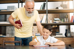 Nonno preoccupantesi che controlla i risultati di compito dei nipoti Immagini Stock