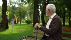 Nonno solo che ricorda la sua infanzia felice, sedentesi nel parco da solo video d archivio