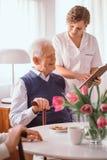 Nonno sorridente che parla del suo programma di giorno con un infermiere nella casa di riposo fotografia stock