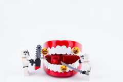 Nonthabure, Thailand - May, 17, 2017 : Lego stormtrooper helping. Get disinfect of bacteria on red plastic chattering teeth isolated on white background stock photo