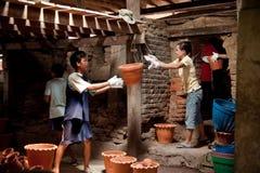 Nonthaburi, Tailandia - 26 aprile 2015: Lavoratori che portano i vasi di argilla dal forno Le piante in vaso hanno bisogno del te Fotografia Stock