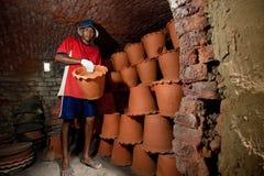 Nonthaburi, Tailandia - 26 aprile 2015: Lavoratori che portano i vasi di argilla dal forno Le piante in vaso hanno bisogno del te Immagini Stock Libere da Diritti