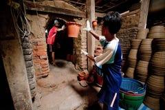 Nonthaburi, Tailandia - 26 aprile 2015: Lavoratori che portano i vasi di argilla dal forno Le piante in vaso hanno bisogno del te Fotografie Stock