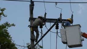Electrician work repair electrical system on electricity pillar or Utility pole. Nonthaburi,Thailand - April 21 : Electrician worker of Metropolitan Electricity stock video
