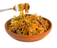 Noodle Beef Stirfry. Fork lifting Noodle Beef Stirfry from serving bowl isolated over white background Royalty Free Stock Photography