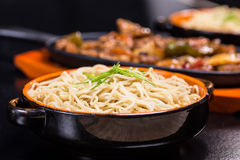 Noodle with blackbean sause pork. Pork in black bean souse with green pepper and onion on the frying pan and noodle in the bowl Royalty Free Stock Photography
