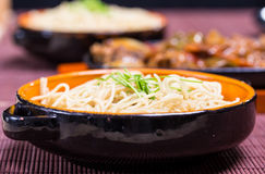 Noodle with blackbean sause pork. Pork in black bean souse with green pepper and onion on the frying pan and noodle in the bowl Royalty Free Stock Photo