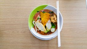Noodle bowl that consist of fish ball, vegetable, soup and more placed on the white cup and disk on the wooden table. In daytime royalty free stock photography