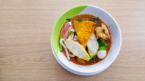 Noodle bowl that consist of fish ball, vegetable, soup and more placed on the white cup and disk on the wooden table. In the restaurant stock photography
