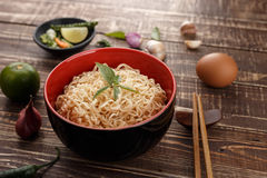 Noodle in bowl and ingredients on wood background side view angl. E Royalty Free Stock Images