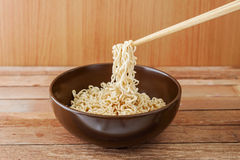 Noodle in brown bowl with wooden chopsticks Stock Image