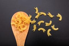 Noodle in a ladle, black background. Noodle pasta in a wooden ladle, black background Royalty Free Stock Photos