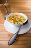 Noodle soup. With carrots on the wooden table Stock Photos