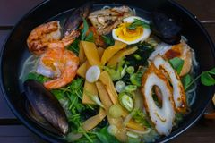 Noodle soup with seafood including mussels, prawns, squids, eggs and vegetables stock photo
