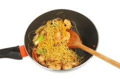 Noodle stir fry in a wok. Noodle, chicken and prawn stir fry in a wok with a wooden spoon isolated against white royalty free stock image
