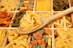 Noodle variation arrangement. Pasta variation - different pasta sorts in wooden box with wooden spoon Stock Image