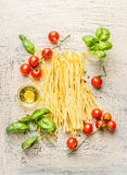 Noodles with basil and tomatoes, ingredients for cooking on light rustic background Royalty Free Stock Photo