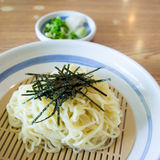 Noodles in bowl. Japanese White Noodles in bowl with dry seaweed Royalty Free Stock Image