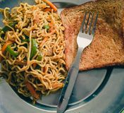 Noodles with bread and a fork royalty free stock images