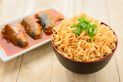 Noodles and canned fish on wooden table Royalty Free Stock Photos