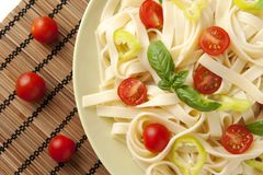 Noodles. With cherry tomatoes, green pepper and basil royalty free stock images