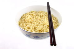 Bowl of noodles and chopsticks. Pair of chopsticks lying on bowl of noodles, white background royalty free stock photos