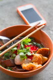 Noodles with fishball and vegetable with red sauce on table Royalty Free Stock Image