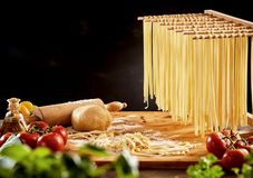 Noodles hanging on wooden rack over cutting board royalty free stock photos