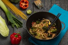 Noodles with meat and vegetables in wok, nearby fresh vegetables on wooden Board Royalty Free Stock Photo