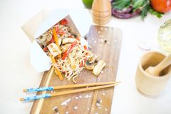 Noodles with mushroom and chicken in take-out box on wooden table. Stir fry noodle with chicken in a wok pan.  Stock Photography