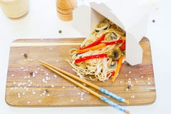 Noodles with mushroom and vegetables in take-out box on wooden table. Noodles with pork and vegetables in take-out box on wooden table Royalty Free Stock Photo