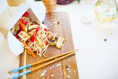 Noodles with mushroom and vegetables in take-out box on wooden table. Noodles with pork and vegetables in take-out box on wooden table Stock Photography