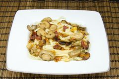 Noodles with mushrooms. Dish of noodles with mushrooms seasoned with Virgin olive oil stock photo