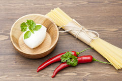 Noodles in paper tied with a rope, a wooden bowl mozzarella, fresh herbs and fresh vegetables Stock Photos