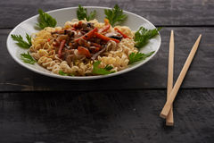 Noodles on a plate and Chinese chopsticks Royalty Free Stock Photos