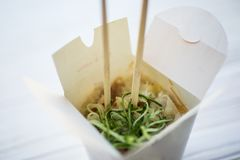 Noodles with pork and vegetables in take-out box on wooden table Stock Photography