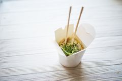Noodles with pork and vegetables in take-out box on wooden table Stock Photo
