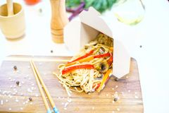 Noodles with mushroom and vegetables in take-out box on wooden table. Noodles with pork and vegetables in take-out box on wooden table Royalty Free Stock Photography
