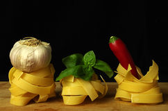 Noodles. Raw italien pasta  with garlic, hot pepper and basil Stock Photo