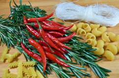Noodles with rosemary and chili. On wooden table stock photography