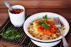Noodles with sauce. Breakfast, noodles, lunch, food, food, sauce, carbohydrates, lunch, dinner, rustic stylein a plate of noodles with a tomato sauce, Chinese Royalty Free Stock Photo