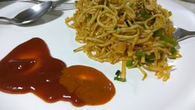 Noodles and sauce. A close up click of a served plate containing veg noodles garnished with ketchup stock images