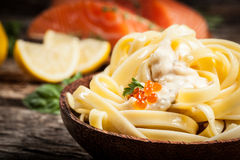 Noodles with sauce and red caviar. On wooden table Royalty Free Stock Image