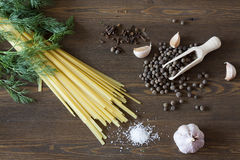 Noodles with spices. Herbs, garlic and tomatoes on a wooden desktop royalty free stock images
