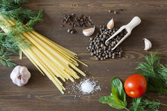 Noodles with spices. Herbs, garlic and tomatoes on a wooden desktop royalty free stock photography