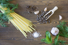 Noodles with spices. Herbs, garlic and tomatoes on a wooden desktop stock photography